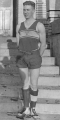 Basketball forward Arthur Kirk in uniform, standing outside, 1920
