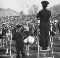 Band leader conducting the marching band on the stadium field, 1960s