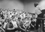A man speaking before a large group of children, 1960s