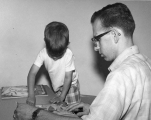 Man helping a young boy put together a puzzle, 1960s.