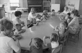 Women and children sitting around table, 1960s