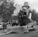 Parade float featuring a farmer smoking a pipe and holding a wheel, 1950s