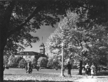 Autumn view of Old Main  and students walking across the Quad, 1960s