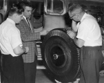 Three men examining machinery, 1960s