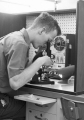 Student looking into microscope, 1950s