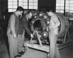 Examining an airplane engine, circa 1952