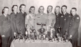 Nine men standing behind a table of trophies, circa 1955
