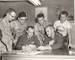 Two ROTC instructors looking over paper targets with cadets, 1950s