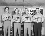 Four men standing, each holding a gun, 1950s