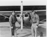 Two ROTC cadets posing by an airplane
