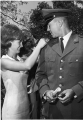 ROTC cadet being commissioned by a young woman, probably his wife, 1960s