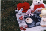 Miranda Gutierres headstone and grave decorations, close-up of left side, Salt Lake City, Utah,...