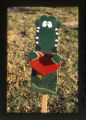 Alligator wooden sign near a grave marker, Salt Lake City, Utah, 2000 (94 of 96)