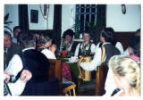 Austrian yodelers and instrumentalists seated around a table in a restaurant in traditional...
