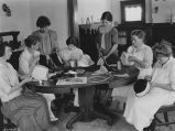 Women sewing hats;