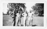 Four men in uniform at a military campsite