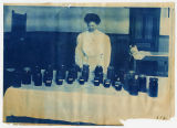 Woman standing in front of bottled goods arranged on table, ACU, 1896-1916