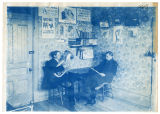 Two men, one playing a baritone, the other reading a book in what appears to be a dorm room,...