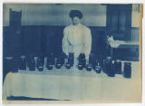 Woman behind table of canned fruits and vegetables that were bottled by students. Duplicate of...