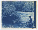 Man in river holding fly fishing rod in one hand and fish in other, ACU, 1896-1916