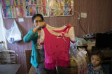 Kaung Lay's wife, Khin Mar Cho holding a pink and white blouse she sewed