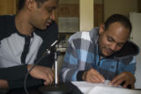 Afeworki Woldemichael signing the release form with Berhane Debesai Abraha, 17 May 2015